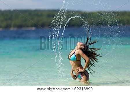 Woman in a bikini flicking her long hair at the seaside as she stands in the shallow surf spraying a graceful arc of water droplets through the air , scenic tropical lagoon in the Philippines