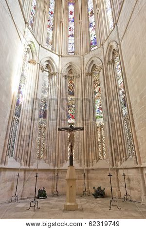 Batalha, Portugal - March 03, 2013: Batalha Monastery. Crucifix and Stained Glass windows in the Apse of the Church. Gothic and Manueline masterpiece. Portugal. UNESCO World Heritage Site.