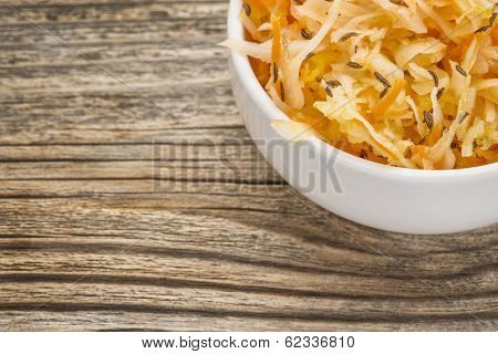 sauerkraut salad with carrot, caraway seeds and olive oil - a small bowl against grained wood