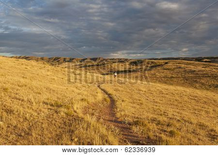 sunrise over Colorado prairie with a distant mountain biking figure - Soapstone Prairie Natural Area, Fort Collins