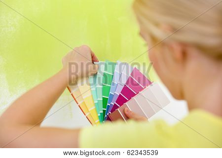 Woman choosing color for painting wall