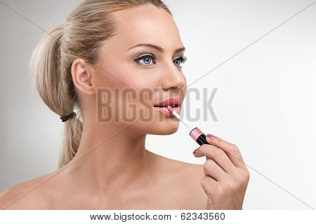 Close-up portrait of young woman applying lip gloss