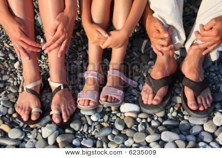 lot of legs and hands on the stones. family with girl
