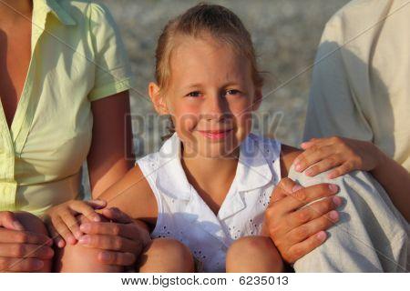 Smiliing daughter sitting between parentson beach