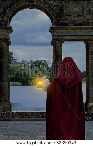 woman waiting by lake with lantern