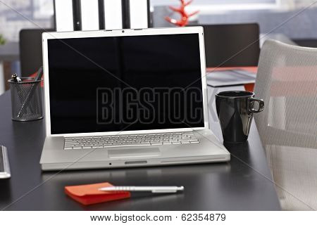 Office desk with laptop and folders.