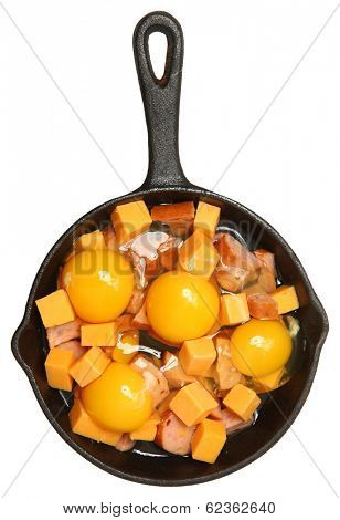 Raw Eggs, Cheese and Sausage in Cast Iron Skillet Isolated Over White.