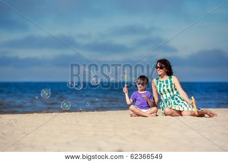 Young mother with his child making soap bubbles
