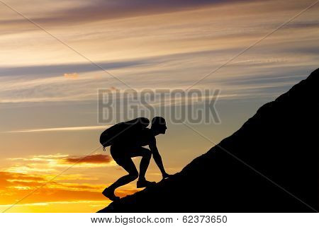 Silhouette Of A Man That Climbs The Mountain On Sunset Sky Background. Climbing A Mountain.