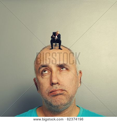 lazy man with small angry businessman on his head
