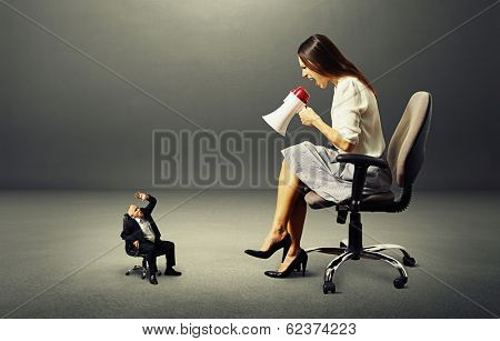 angry young woman and small frightened man over dark background