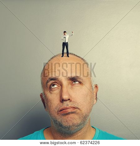 tired senior man with small angry businessman on his head