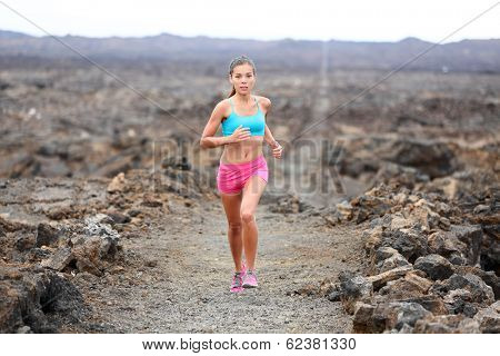 Runner woman triathlete trail running cross country running outdoors on volcano. Female athlete jogging training for marathon run outside in beautiful landscape on Big Island, Hawaii, USA.