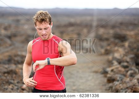 Running athlete man looking at heart rate monitor GPS watch. Runner listening to music in earphones. Athlete resting tired after training on Big Island, Hawaii, USA.