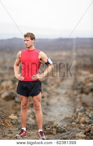 Runner man - portrait of running athlete resting after cross country run on trail. Fit handsome male triathlete taking break standing relaxing in beautiful volcano landscape on Big Island, Hawaii, USA