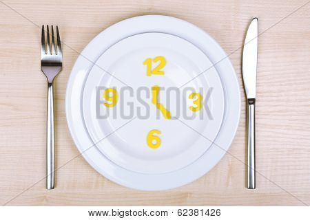 Plate with clock on wooden table close-up