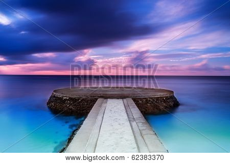 Beautiful pier in sunset, dramatic purple and blue cloudy sky, place for romantic dinner, luxury resort on Maldives, summer vacation concept