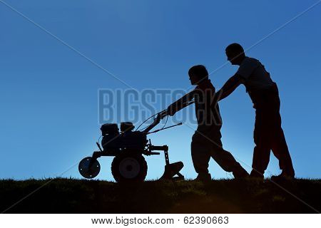 Father And Son Working The Land With A Tiller