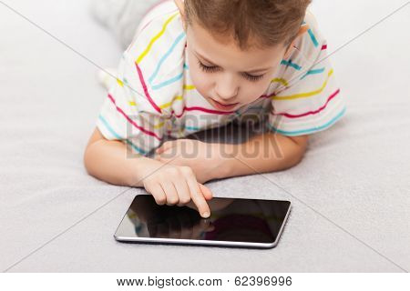 Little smiling child boy playing games or surfing internet on digital tablet computer