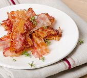 foto of bacon strips  - Cooked bacon rashers on a white plate - JPG