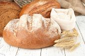 Rye bread with flour on table on sackcloth background