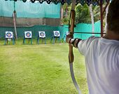 stock photo of longbow  - Archer man pulls the bowstring and arrow aiming at a target - JPG