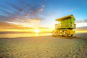 stock photo of lifeguard  - Miami South Beach sunrise with lifeguard tower and coastline with colorful cloud and blue sky.