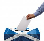 Scottish independence referendum ballot box covered in scotlands flag with person casting vote on bl