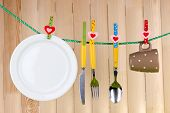 Tableware dried on rope on wooden background