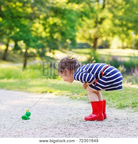 Beautiful Little Girl In Red Rain Boots Playing With Rubber Frog.