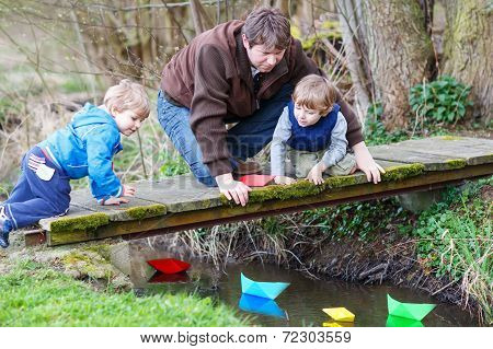 Two Little Brothers And Their Dad Playing With Paper Boats By A River