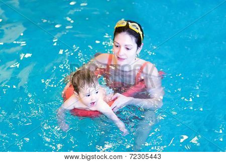 Little Baby Swimming In A Pool With Her Mother