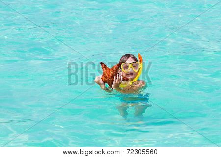 Little Boy Playing With A Star Fish On A Tropical Beach