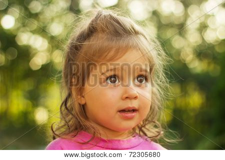 Cute little kid looking with interest in a shiny background