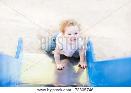 Laughing Baby Girl Playing On A Slide