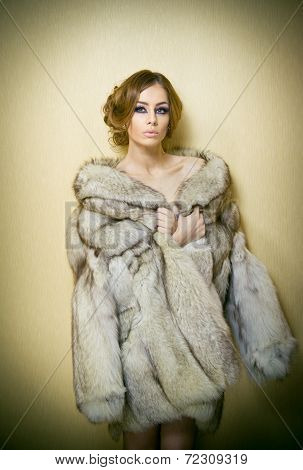 Attractive sexy young woman wearing a fur coat posing provocatively indoor