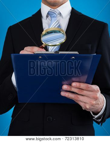 Businessman Examining Document With Magnifying Glass