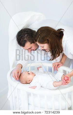 Happy Young Parent Looking At Their Baby Son In A White Round Crib