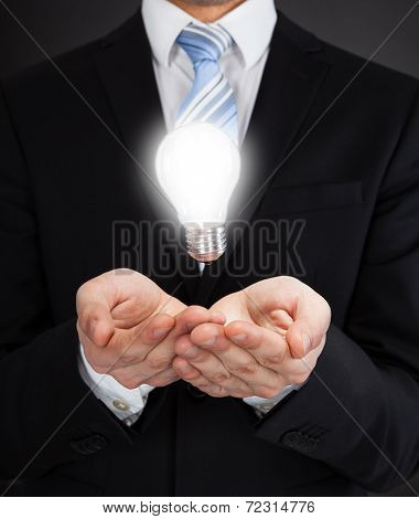 Businessman With Glowing Bulb Representing Ideas