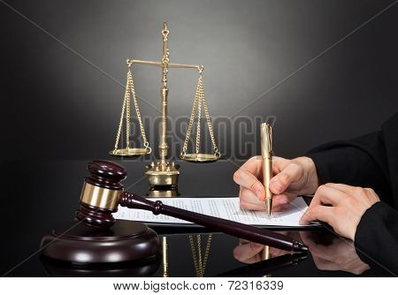 Male Judge Signing Document At Desk