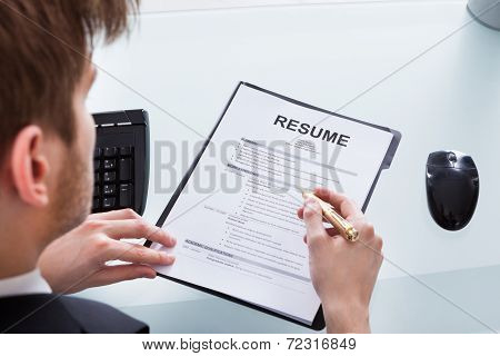 Businessman Analyzing Resume At Office Desk