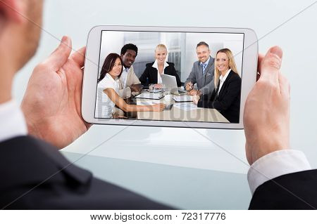 Businessman Video Conferencing On Digital Tablet At Desk