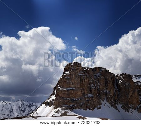 Panorama Of Snowy Rocks And Sky With Sunbeam In Nice Spring Day
