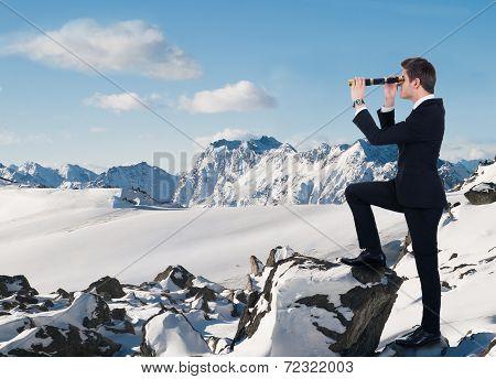 Businessman Looking Through Handheld Telescope In Snow