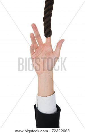 Businessman's Hand Trying To Reach Rope
