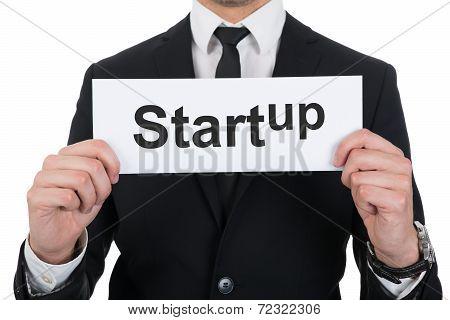 Businessman Holding Startup Sign