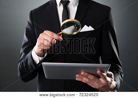 Businessman Analyzing Digital Tablet With Magnifying Glass