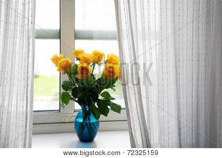 Fresh bouquet of yellow roses in a blue glass vase, on a windowsill