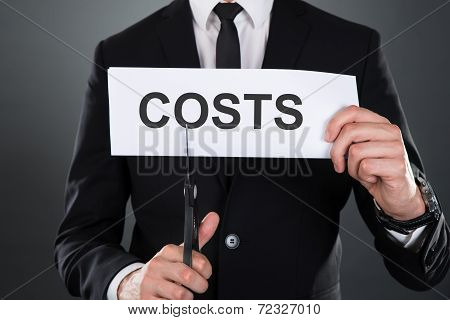 Businessman Cutting The Word Costs On Paper With Scissors