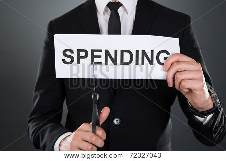 Businessman Cutting The Word Spending On Paper With Scissors